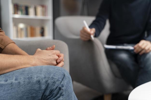 Deux personnes échangent dans le cadre d'un cabinet thérapeutique. Zoom sur leurs buste/avant bras, le cadre ne montre pas leurs visages. Image issue du site Freepick.